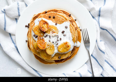 Pancakes with caramelized bananas, natural yogurt, chocolate chips and coconut shavings on white plate. Top view - Stock Photo
