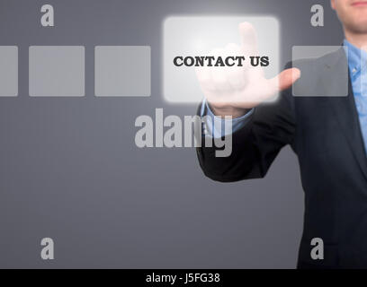 Businessman hand pushing contact us button on a touch screen interface. Grey - Stock Photo - Stock Photo