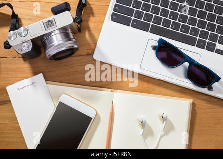 digital photography or planning photo vacation concept, showing items such as camera, computer, phone, and notebook - Stock Photo