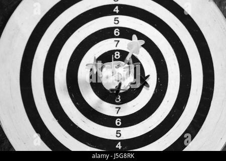 Black and white dart board with darts in the center. - Stock Photo