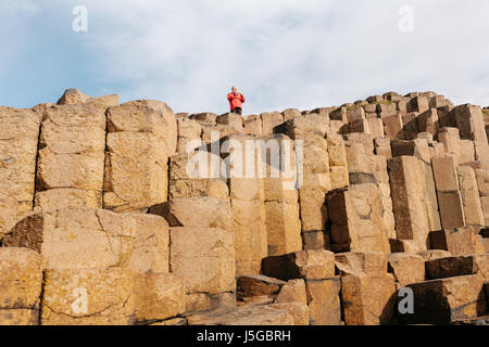 Male Tourist wearing a red jacket at The Giant's Causeway. - Stock Photo