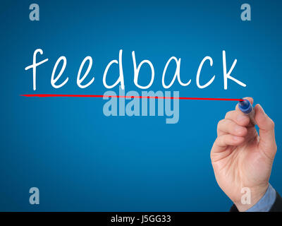 feedback concept with businessman hand writing. Isolated on blue background. Stock Image - Stock Photo