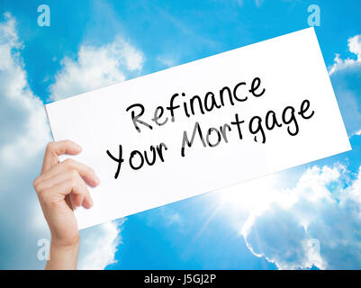 Refinance Your Mortgage Sign on white paper. Man Hand Holding Paper with text. Isolated on sky background.  Business - Stock Photo