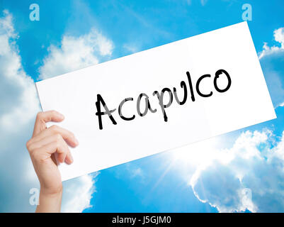 Acapulco  Sign on white paper. Man Hand Holding Paper with text. Isolated on sky background.  Business concept. - Stock Photo