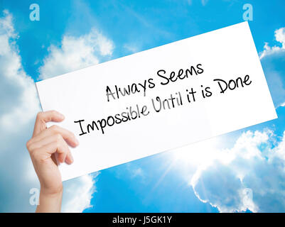Always Seems Impossible Until it is Done Sign on white paper. Man Hand Holding Paper with text. Isolated on sky - Stock Photo