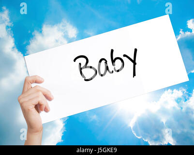 Baby Sign on white paper. Man Hand Holding Paper with text. Isolated on sky background.  technology, internet concept. - Stock Photo