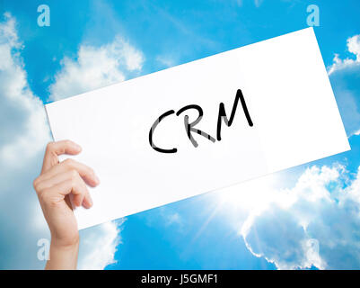 CRM Sign on white paper. Man Hand Holding Paper with text. Isolated on sky background.   Business concept. Stock - Stock Photo