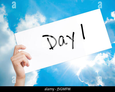 Day 1 Sign on white paper. Man Hand Holding Paper with text. Isolated on sky background.  Business concept. Stock - Stock Photo