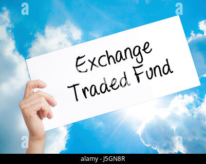 Exchange Traded Fund Sign on white paper. Man Hand Holding Paper with text. Isolated on sky background.  Business - Stock Photo