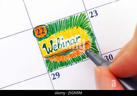 Woman fingers with pen writing reminder Webinar in calendar. - Stock Photo