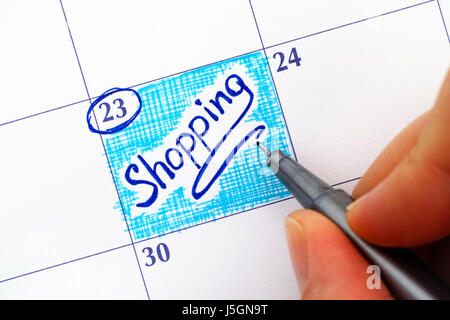 Woman fingers with pen writing reminder Shopping in calendar. - Stock Photo