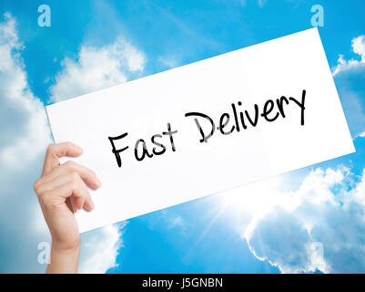 Fast Delivery Sign on white paper. Man Hand Holding Paper with text. Isolated on sky background.   Business concept. - Stock Photo
