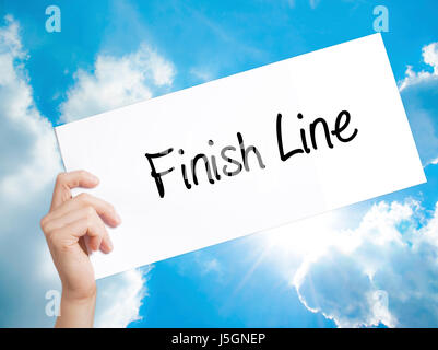Finish Line Sign on white paper. Man Hand Holding Paper with text. Isolated on sky background.  technology, internet - Stock Photo