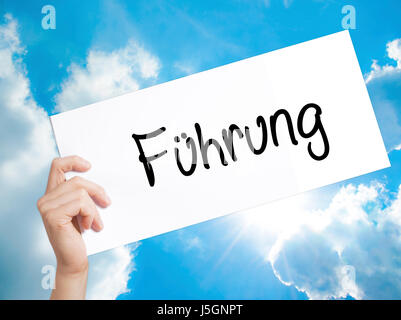 Fuhrung (Leadership in German) Sign on white paper. Man Hand Holding Paper with text. Isolated on sky background. - Stock Photo