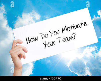 How Do You Motivate Your Team? Sign on white paper. Man Hand Holding Paper with text. Isolated on sky background. - Stock Photo