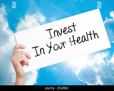 Invest In Your Health Sign on white paper. Man Hand Holding Paper with text. Isolated on sky background.  Business - Stock Photo