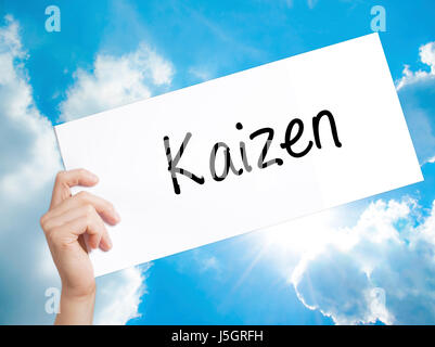 Kaizen Sign on white paper. Man Hand Holding Paper with text. Isolated on sky background.   Business concept. Stock - Stock Photo