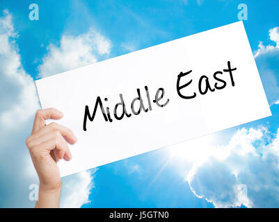 Middle East Sign on white paper. Man Hand Holding Paper with text. Isolated on sky background.   Business concept. - Stock Photo