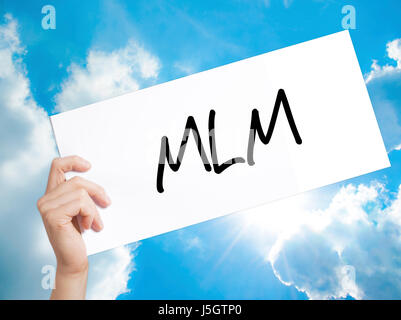 MLM (Multi-Level Marketing) Sign on white paper. Man Hand Holding Paper with text. Isolated on sky background.  - Stock Photo