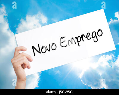 Novo Emprego (New Job in Portuguese)   Sign on white paper. Man Hand Holding Paper with text. Isolated on sky background. - Stock Photo