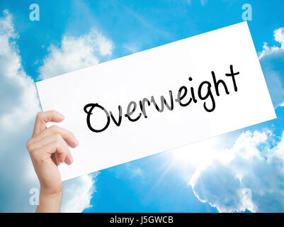 Overweight  Sign on white paper. Man Hand Holding Paper with text. Isolated on sky background.   Business concept. - Stock Photo