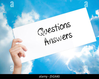 Questions Answers Sign on white paper. Man Hand Holding Paper with text. Isolated on sky background.   Business - Stock Photo