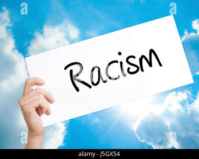 Racism Sign on white paper. Man Hand Holding Paper with text. Isolated on sky background.  Business concept. Stock - Stock Photo