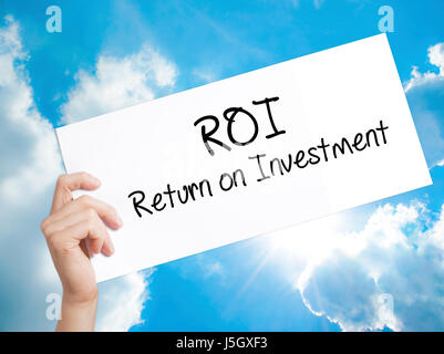 ROI  Return on Investment Sign on white paper. Man Hand Holding Paper with text. Isolated on sky background.   Business - Stock Photo