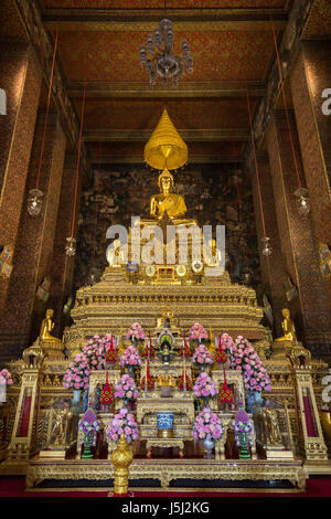 Ornate and golden altar inside the Phra Ubosot or Ordination Hall, which is the holiest prayer room at the Wat Pho - Stock Photo