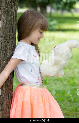 The little girl leaning against a tree holding her favorite stuffed toy