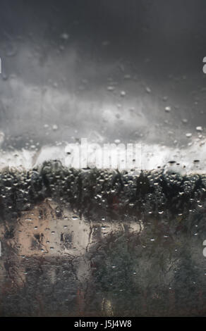 View of the house through the glass in the rain - blur - Stock Photo