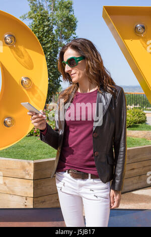 brown hair woman with white jeans, red shirt, leather blazer jacket and sunglasses, standing in urban park, looking - Stock Photo