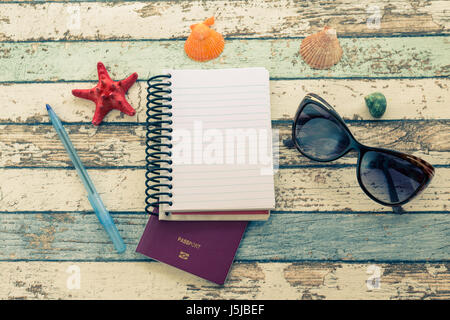 Travel concept: passport, sunglasses, notebook, and seashells top view - Stock Photo