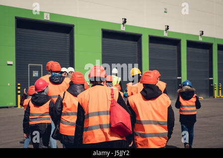 A group of people in orange helmets and reflective vests visiting factory or warehouse. From behind view. - Stock Photo