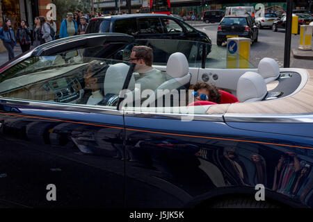 Wealthy adults and a child wearing sunglasses who smiles in the back of an open-top car remaining stationary at - Stock Photo