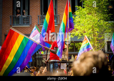NEW YORK CITY - JUNE 26, 2015: Supporters wave rainbows flags on the sidelines of the annual Pride Parade as it - Stock Photo