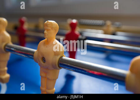 An old fussball, foosball or table football game which has painted white and red players - Stock Photo