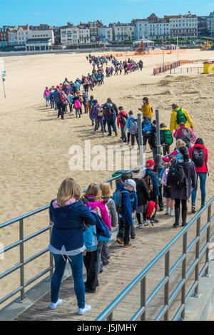 A long line of young school children with their teachers and helpers on a daytrip walking across the beach at Margate, - Stock Photo