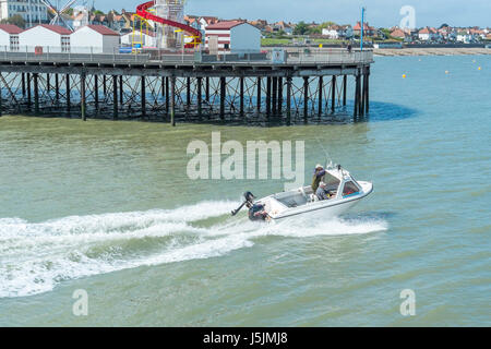 Two men on a small powerboat heading out for a fishing trip in the English channel. Herne Bay pier is in the background. - Stock Photo