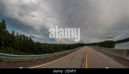 View of empty road through the Lake and forest with storm in the sky - Stock Photo