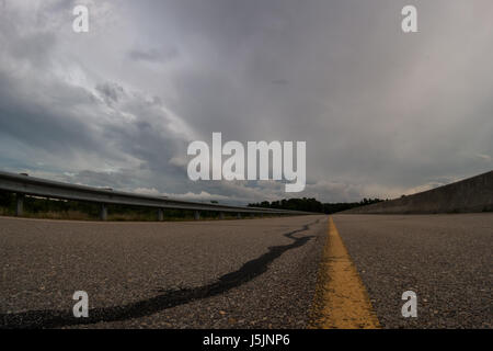 Storm at the distance, with deserted road in the foreground - Stock Photo