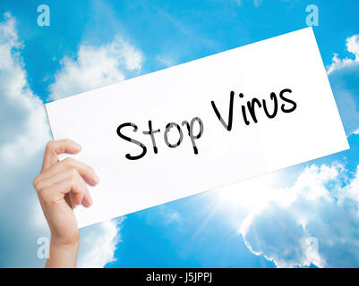 Stop Virus Sign on white paper. Man Hand Holding Paper with text. Isolated on sky background.   Business concept. - Stock Photo