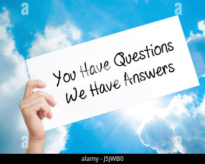 You Have Questions We Have Answers Sign on white paper. Man Hand Holding Paper with text. Isolated on sky background. - Stock Photo