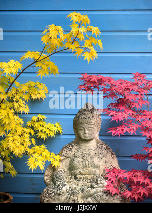 Oriental garden feature with stone Buddha and Japanese Maples, Acer Palmatum in peaceful reflective setting with - Stock Photo