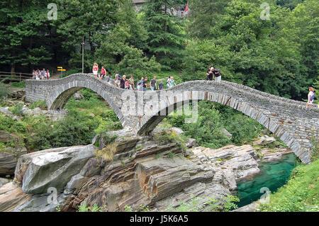 Tourists admire the double arch stone Roman bridge Ponte dei Salti - Stock Photo