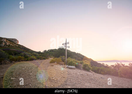 Rural scenic landscape with crossroad on hill in forest at sunset. Two different directions. Concept of choose the - Stock Photo