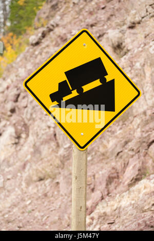 Sign with a truck going down a wedge shape on the roadside - Stock Photo
