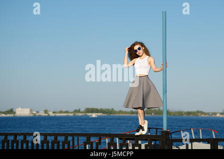 Young attractive girl hipster dancing on the pole. She is wearing a top, a skirt and sunglasses. The concept of - Stock Photo
