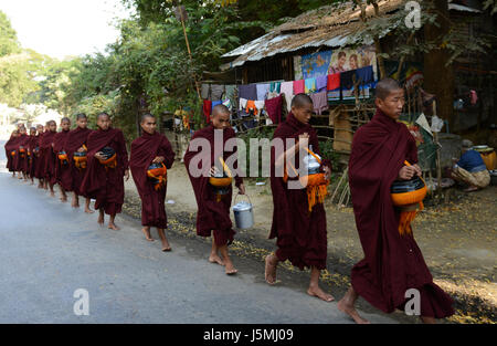 Burmese Buddhist monks collecting alms, an everyday morning ritual. - Stock Photo
