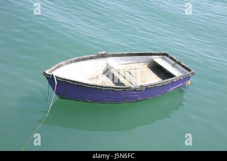 a single rowing boat moored on a calm sea. - Stock Photo